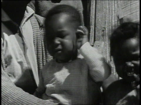 1939 CU child scratching ear outside school / Lowndes County, Alabama, United States