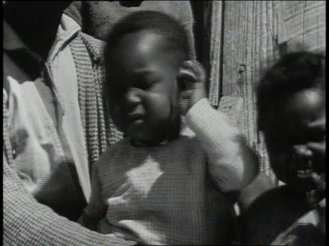 1939 cu child scratching ear outside school / lowndes county, alabama, united states - 分校点の映像素材/bロール