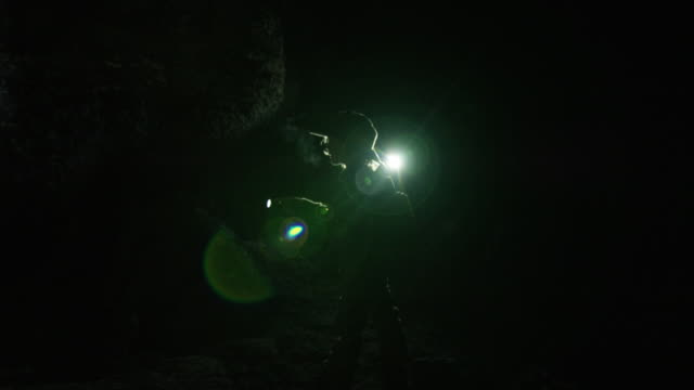 child shines flashlight in dark cave - electric torch stock videos & royalty-free footage