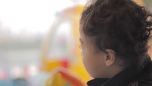 vídeos de stock e filmes b-roll de criança cantar, concordar, murmuring no carrossel assembleia, grande dof, de recreio, - equipamento de parque infantil