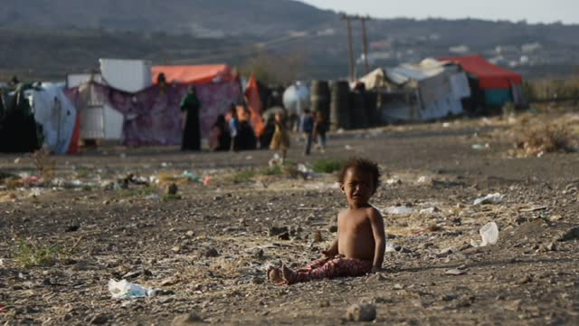 child sits on the ground as persons who were displaced due to the ongoing war stand beside their tents at an internally displaced camp on february 21... - yemen stock videos & royalty-free footage