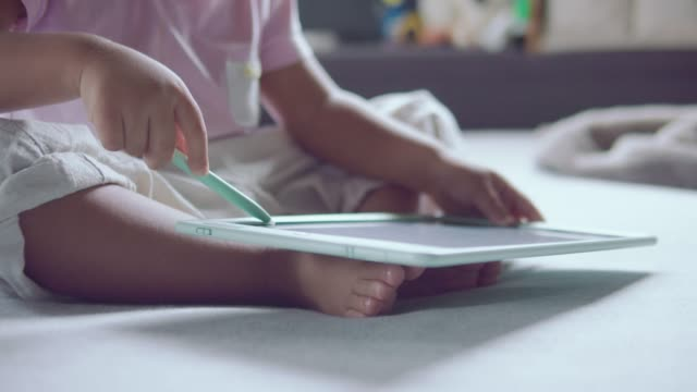 child sitting drawing with digital tablet on the bed. - giocattolo video stock e b–roll