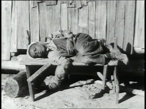 child sleeping outdoors on bench / children attending cauldron cooking pot