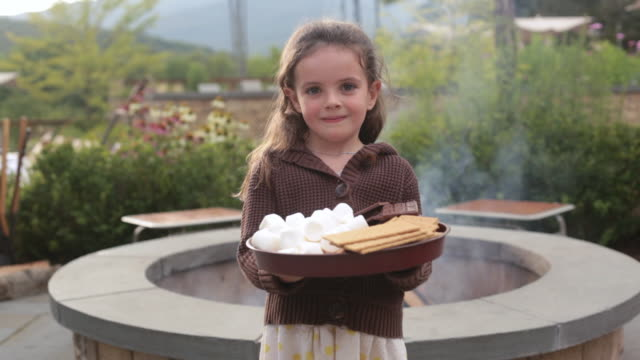 ms child standing in front of fire pit holding tray with marshmallows, graham crackers, and chocolate / stowe, vermont - stowe vermont stock videos & royalty-free footage