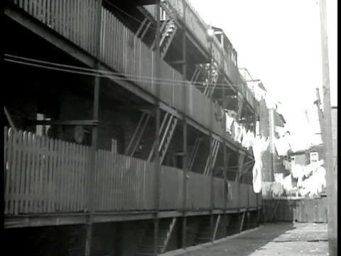 child standing near wooden wall wooden apartment houses w/ laundry hanging on line demolishing city buildings men demolishing multistory buildings by... - 1946 stock videos and b-roll footage