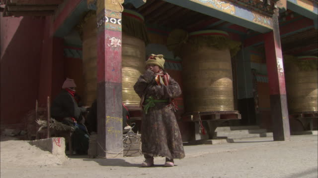 A child stands near the huge bells of a temple in Tibet.