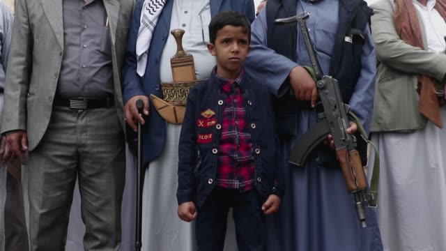 child stands with followers of the houthis group take part in a tribal gathering against the saudi-led coalition war on yemen on july 06, 2020 in... - 武器庫点の映像素材/bロール