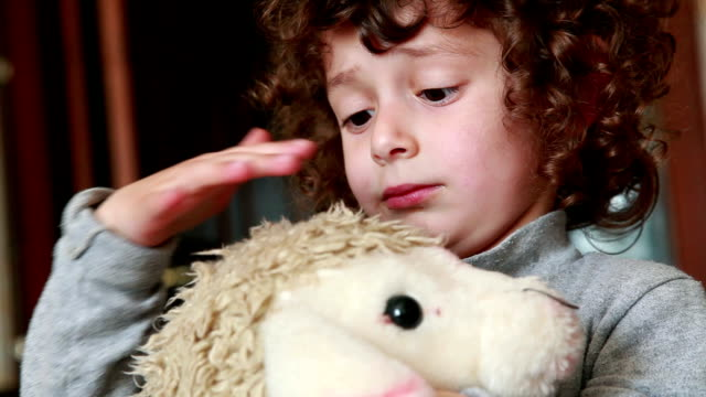 Child stroking a toy lamb