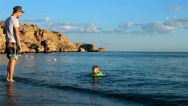 子供は海で泳ぐ。父は娘の後を見る。 - 浮き輪点の映像素材/bロール