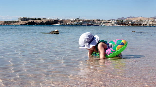 child swims with an inflatable circle in the red sea. egypt. - red sea stock videos & royalty-free footage