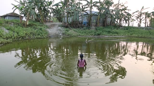 stockvideo's en b-roll-footage met a child taking a bath in a pond during rainy season their houses are eroded by flood and they shift to another places - vluchteling ontheemden