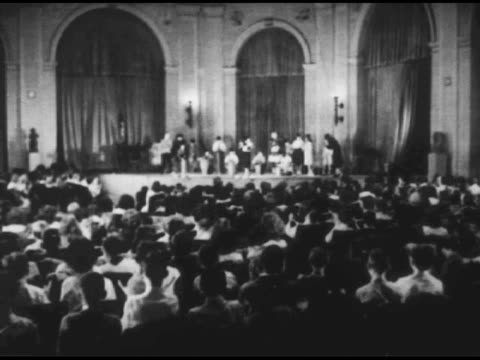 vídeos de stock, filmes e b-roll de / child theater audience clapping / young boys banging tribal drums / distant shot of theater stage / stack of museum flyers / young girls at... - 1951