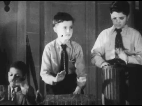 vídeos de stock, filmes e b-roll de / child theater audience / young boys banging makeshift drums / distant shot of theater stage / panning shot of young girls playing makeshift... - 1951