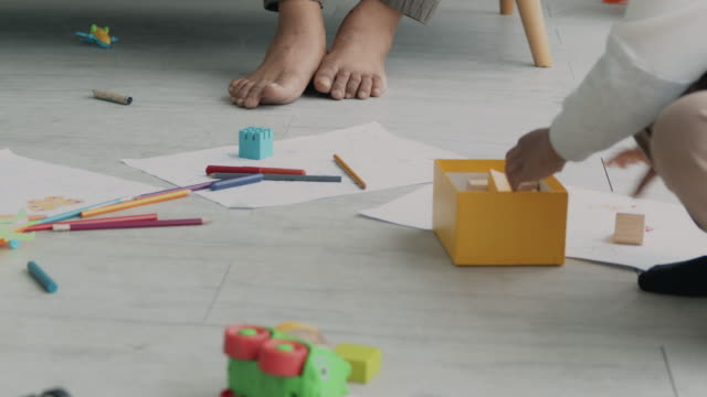 child tidy up his toy in living room. candid handheld shot. - tidy room stock videos & royalty-free footage