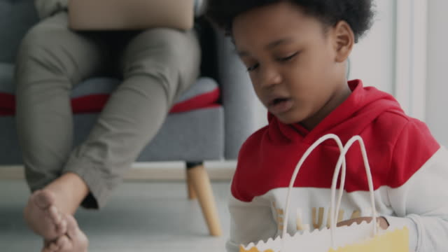 child tidy up his toy in living room while father working on laptop. candid handheld shot. - tidy room stock videos & royalty-free footage