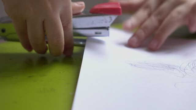 子を使用して、ホチキス、スタックのペーパーズ - ホッチキス点の映像素材/bロール