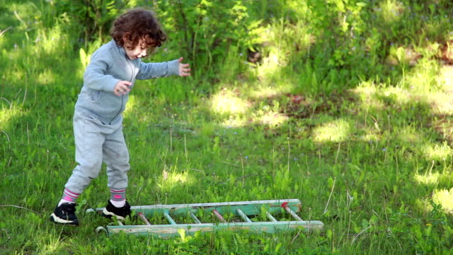 child trying to walk on the wooden ladder in the lawn - lawn stock videos & royalty-free footage