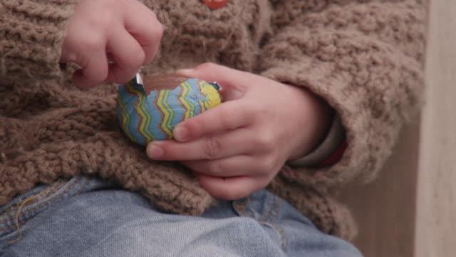 vidéos et rushes de child unwraps chocolate during easter egg hunt, bristol, england - pâques
