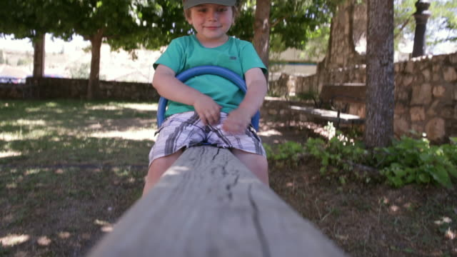 child (3 years od) up and down on a seesaw - segovia stock videos & royalty-free footage