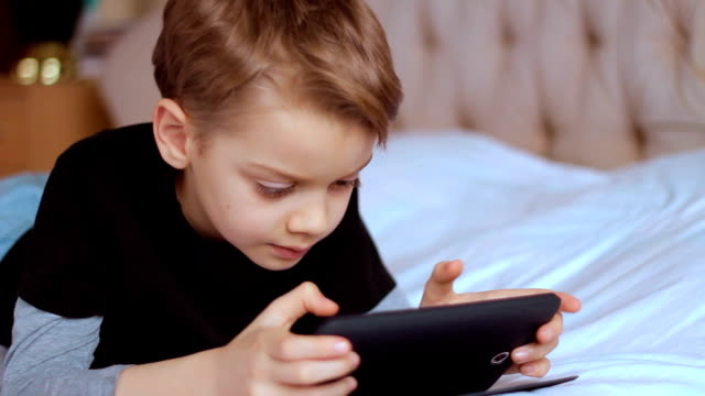 child using digital tablet alone at home, playing game - one boy only stock videos & royalty-free footage