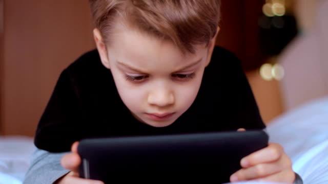 vídeos y material grabado en eventos de stock de hijo usando tableta digital solo en casa, jugando juegos - malos hábitos