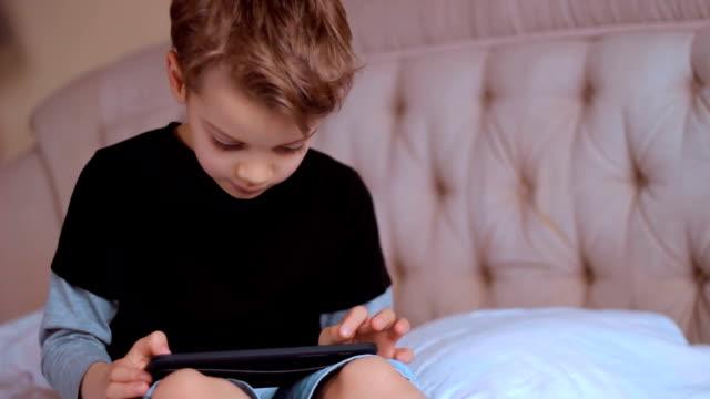 Kind mit tablet PC, allein zu Hause, beim Spielen