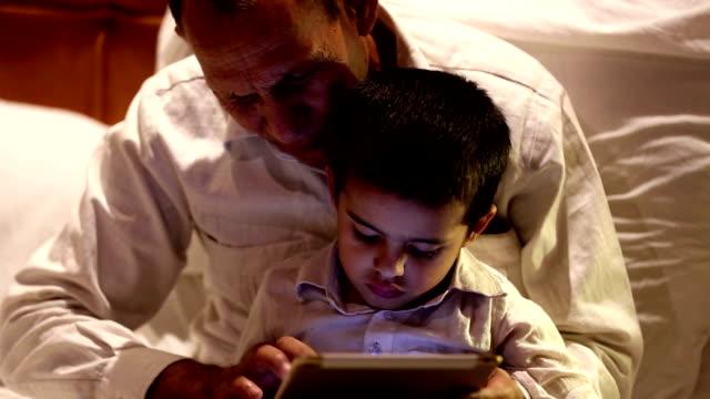Child using ipad with grandparent portrait indoor