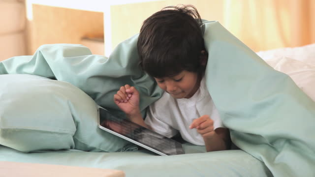 ms child using tablet computer in bed / richmond, virginia, united states - bedtime stock videos & royalty-free footage