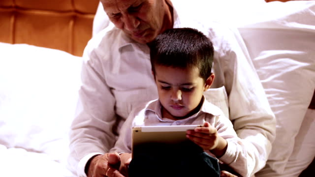 child using ipad with grandfather - nursery bedroom stock videos & royalty-free footage