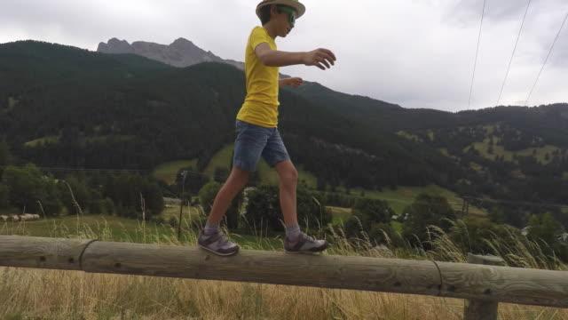vidéos et rushes de child walk on a wooden beam - stabilité
