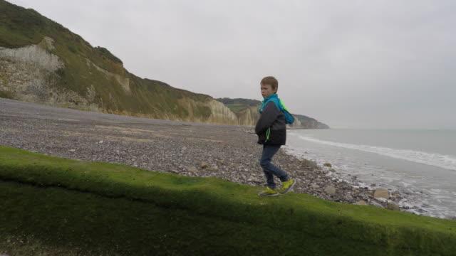 vidéos et rushes de child walking by the sea - profil