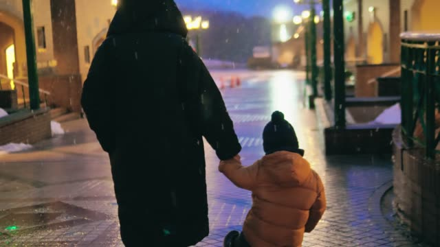 child walking with mother in night with snow on city street. - pedestrian stock videos & royalty-free footage