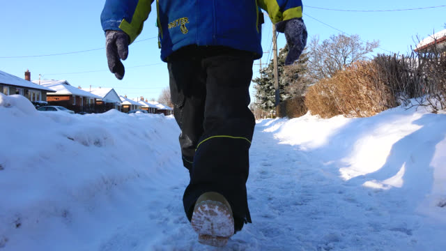 child walks in the city sidewalk with a thick branded winter clothing seen on december 10, 2015; in toronto, ontario. canada. it is a blue sky day... - one boy only stock videos & royalty-free footage