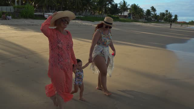child walks on the shore with mother and grandmother - swimming costume stock videos & royalty-free footage