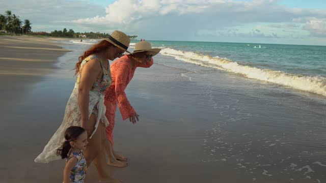 child walks on the shore with mother and grandmother - tropical climate stock videos & royalty-free footage