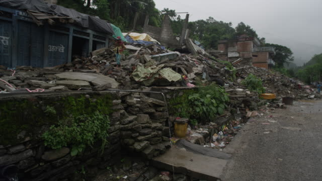 barabise, nepal - july 31, 2015: child walks over rubble in destroyed street to water pipe - rubble stock-videos und b-roll-filmmaterial