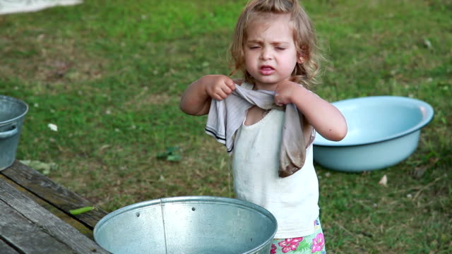 child washing a dirty sock in the backyard - adult imitation stock videos and b-roll footage