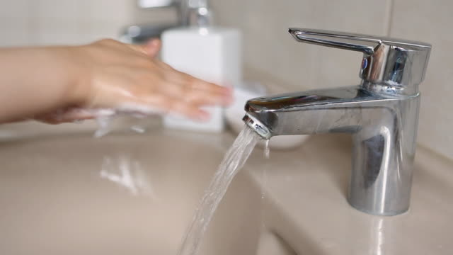 Child washing hands with soap under a running tap