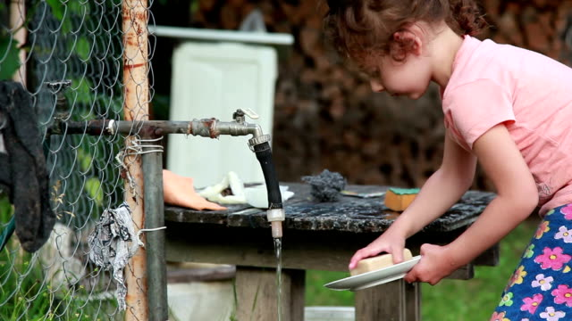 child washing the dish in the backyard - adult imitation stock videos and b-roll footage