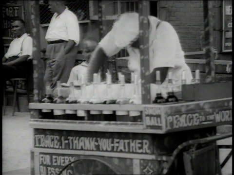 1938 WS child watching street vendor shaving ice, his cart reads Peace: I thank you father / New York City, New York, United States