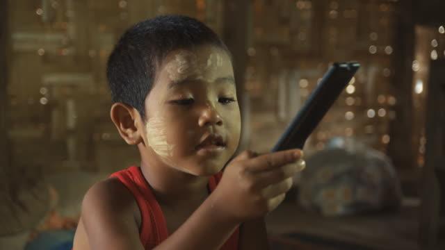 m/s child (boy) watching tv and using remote control - テレビのリモコン点の映像素材/bロール