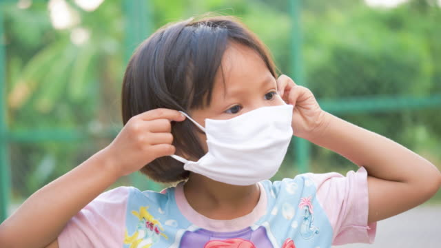 child wear face mask during coronavirus a mask protecting her from covid19. - puebloan peoples stock videos & royalty-free footage