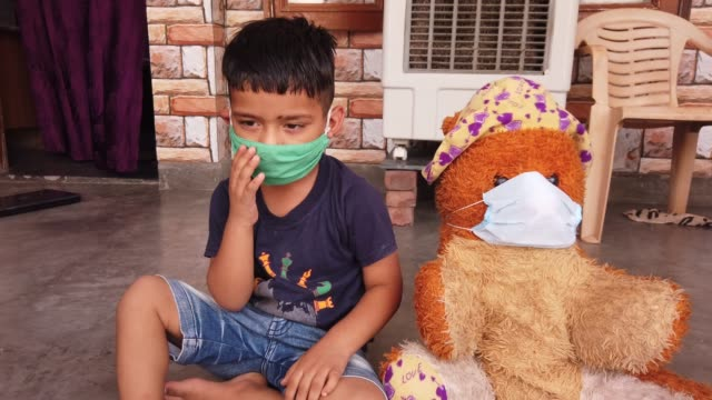 stockvideo's en b-roll-footage met child wearing a mask along with his stuffed toy teddy bear also wearing a mask during the coronavirus pandemic lockdown at home quarantine - alleen jongens