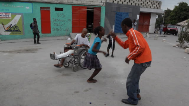 stockvideo's en b-roll-footage met a child with a broken leg watches friends jump rope after the earthquake. - haïti