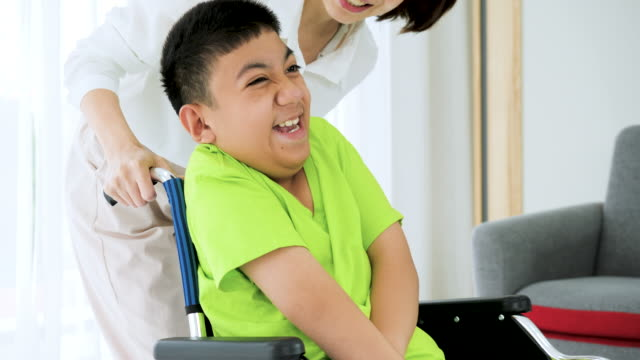 child with a physical disability sitting and laughing on wheelchair with home caregiver. - cerebral palsy stock videos & royalty-free footage