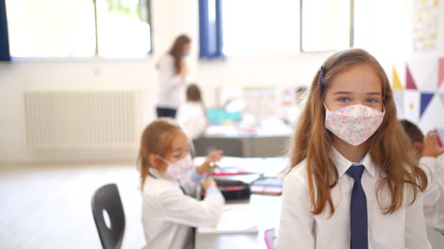 child with face mask back at school after covid-19 quarantine and lockdown - uniform stock videos & royalty-free footage