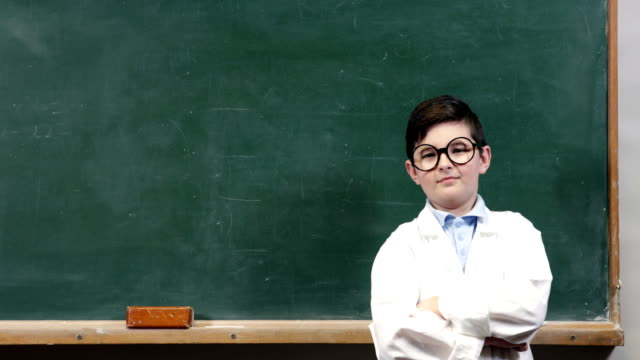 Child with funny glasses showing imaginary items on the blackboard