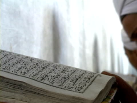cu child with koran open, shitral valley, north west province, pakistan - koran stock videos and b-roll footage