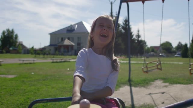 child with mother on a playground carousel at summer recess - 30 seconds or greater stock videos & royalty-free footage