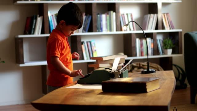 vídeos y material grabado en eventos de stock de niño con máquina de escribir - periodista